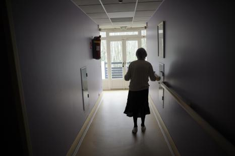 A woman, suffering from Alzheimer's desease, walks in a corridor on March 18, 2011 in a...